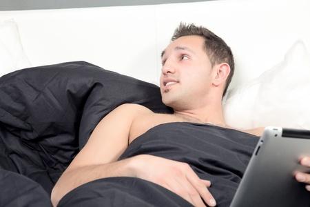 quizzical: El hombre tumbado en la cama wih un tablet-PC en sus manos mirando hacia arriba a la izquierda de la imagen con una expresi�n burlona