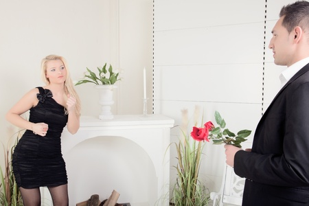 assignation: Romantic couple dating with the beautiful blond woman in a stylish black dress watching her beau approaching holding a single red rose, interior living room shot