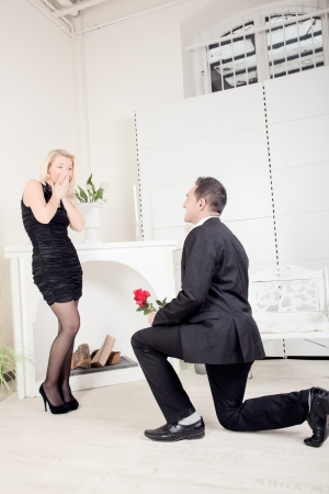 Romantic man proposing to his shocked girlfriend kneeling down on the floor in front of her with a rose and the ring box in his hand photo