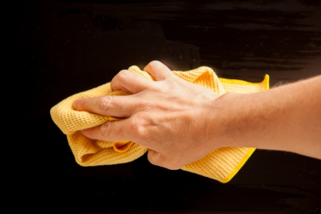 The TV is cleaned by a a woman with a yellow duster. photo