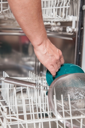 washup: A middle aged girl in the kitchen is using the dishwasher. Stock Photo