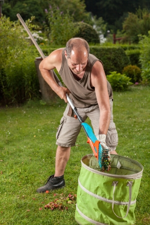 The gardener is filling the trash with some leaves. photo