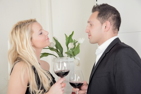 courting: Couple celebrating with glasses of red wine standing in profile smiling into each others eyes