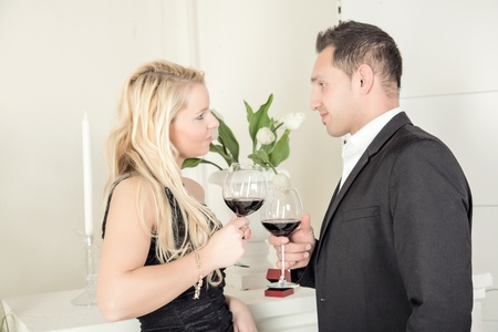 'evening wear': Loving couple in evening wear standing toasting each other with large glasses of red wine as they celebrate together