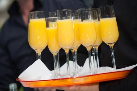 The waitress filled up some glasses of orange juice  photo