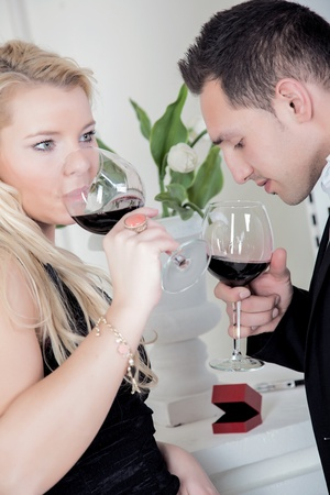 A young couple is tasting a glass of wine  photo