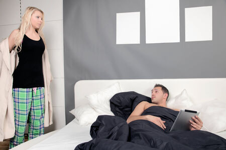 Woman standing at the side of the bed undressing and removing her dressing gown to join her husband under the bedclothes photo