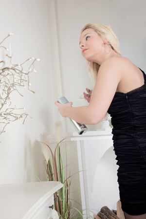 eveningwear: Woman spraying her long blond hair with hairspray as she dresses for a night out in a stylish black dress Stock Photo