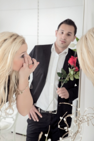 suitor: Romantic man carrying a single long stemmed red rose reflected in a mirror admiring and watching his sweetheart is she titivates in the mirror