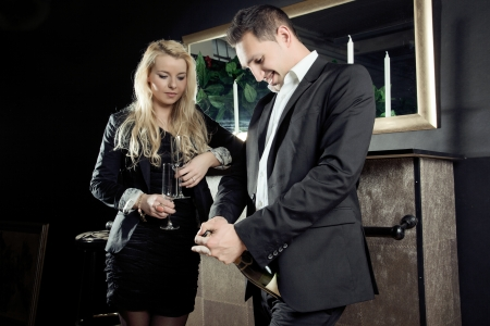 assignation: Young man pouring festive champagne into a stylish flute while watched in anticipation by his beautiful female partner who is holding an empty glass