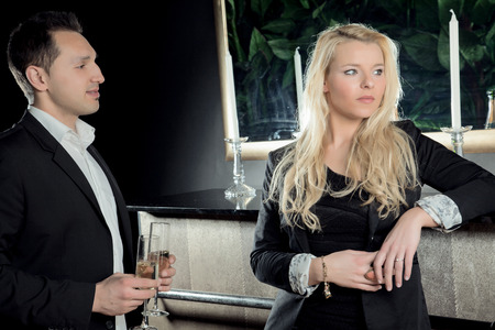 A young man wants to clink the glasses with a blond woman  Stock Photo