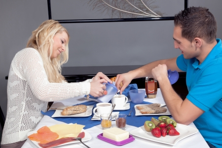 Attractive couple enjoying breakfast at home with coffee, bread, butter, cheese, honey and fruit photo