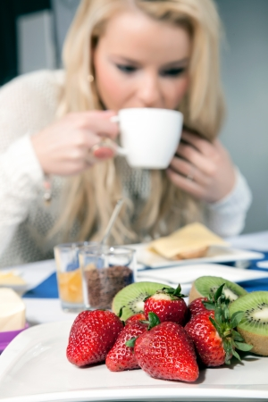 Serving of fresh strawberries and kiwifruit on a white platter on a breakfast table as a healthy appetizer with a blond woman drinking coffee in the background, shallow dof photo