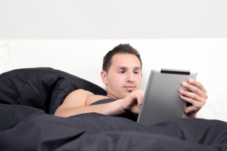 recuperating: An attractive young business man is working in there bed  Stock Photo
