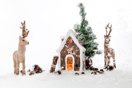 brushwood: Two reindeers near a Gingerbread House at a snowy day