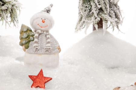 somebody: A Snowman is watching to a XMas Star which is maybe forgotten from somebody else  Stock Photo