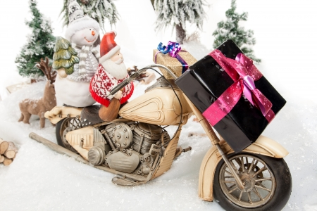 Santa Claus and a Snowman are delivering some Christmas present on their motor-bike  photo