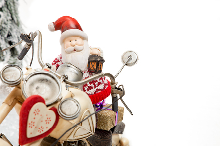 Santa Claus delivers some XMas Gifts on his Motocycle to the clients in a winter Scenery with a lot of copyspace