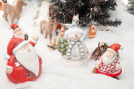 Santa Claus is doing a meeting before Christmas starts  Reindeers, a snowman and some other Santa Clauses are involved  photo