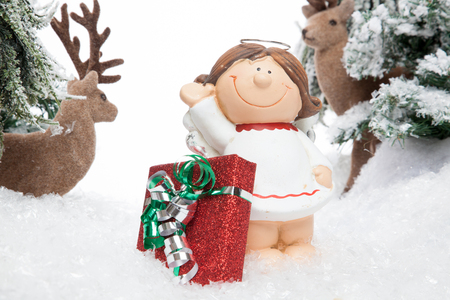 viewing angle: A smiling cartoon child guarded by two reindeers presents a X-Mas Gift