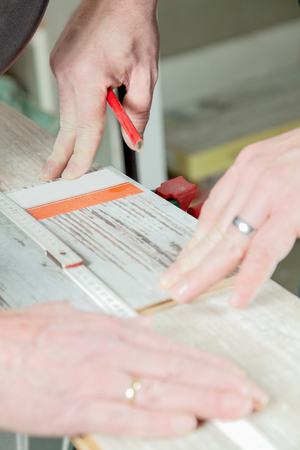 build buzz: A man is measuring the correct length of the laminate panel