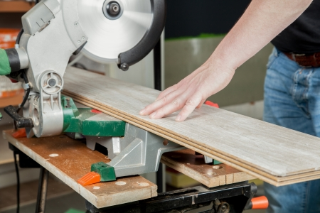 build buzz: A man is sawing a piece of laminate with a buzz saw