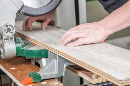 build buzz: A Carpenter is cutting the laminate with a buzz saw
