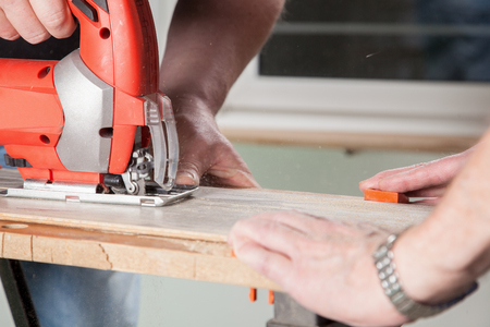 Two Peoples are sawing a piece of Laminate  photo