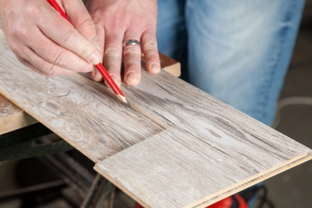 build buzz: A carpenter use a cutted piece of laminate for marking an other one before cutting