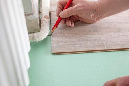 build buzz: A Man is marking a piece of laminate before cutting
