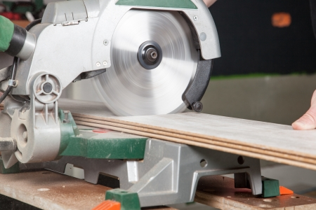 build buzz: A buzz saw is sawing two pieces of laminate at the same time