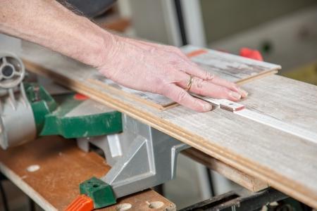 build buzz: A Man is measuring the correct length of a laminate