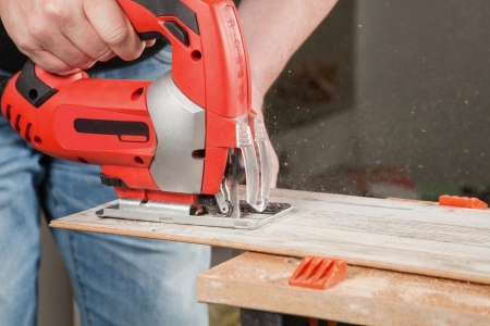 A man is sawing a piece of Laminate which is fixed in a bench vice  Stock Photo