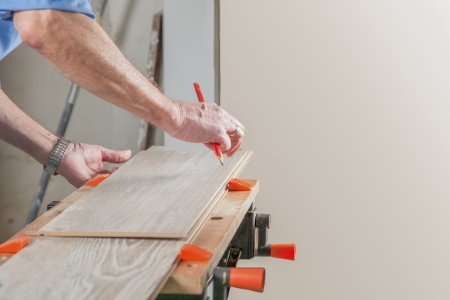 build buzz: A Carpenter is preparing a piece of laminate before sawing