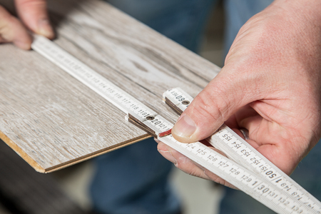 build buzz: A Carpenter is measuring the right length of the laminate