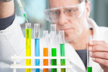 injurious: A Chemist is refilling the test tube with a yellow liquid