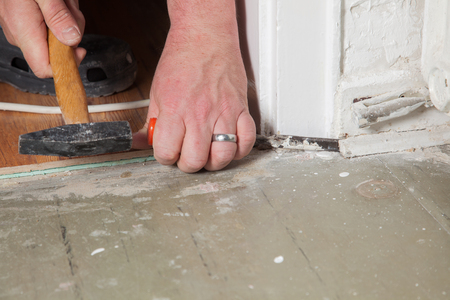 A Man is carving the old baseboard from the wall