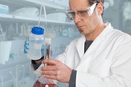 A Chemist is mixing two liquids in a glass container  photo