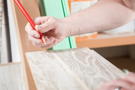 build buzz: The Carpenter is drawing a line on the laminate. Stock Photo
