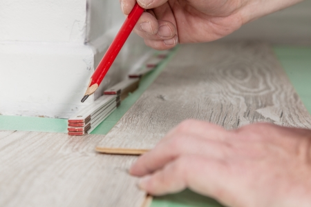 build buzz: A Man is measuring the right distance to the wall before sawing the wood.