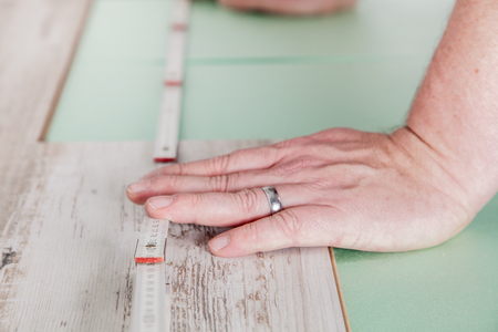 build buzz: A worker measures the perfect length for the laminate