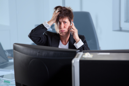 A Business woman is stressed out during a phone call  photo