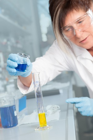 The Laboratory Assistant is decanting a blue liquid into a Test Tube with a yellow Liquid  photo