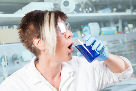 A Chemist is making a big mistake  SHe mixed a chemical liquid with a drink  photo