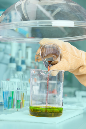 The Chemist is mixing a greenish substance  photo
