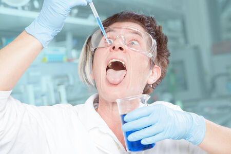 abnormal: A Chemist is showing an abnormal behavior in her laboratory  Stock Photo
