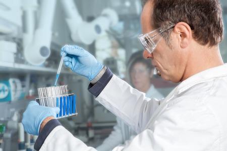 test probe: Professore estrae una sonda liquido blu da una provetta piena