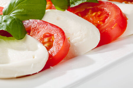 Tomatoes and mozzarella slices well stringed  photo