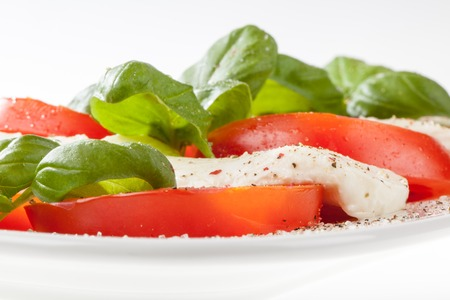 A vegetarian salad with mozzarella and tomatoes decorated with some basil  photo