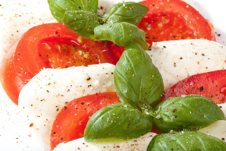 Some Tomatoes stacked with mozzarella and basil  photo
